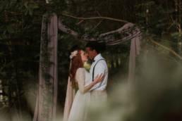 mariage bohème dans les bois, arche de mariage en bois et voilage